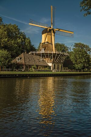 House and wooden yellow windmill next to wide tree-lined canal on the bright light of sunset at Weesp. Quiet and pleasant village full of canals and green near Amsterdam. Northern Netherlands. 스톡 콘텐츠