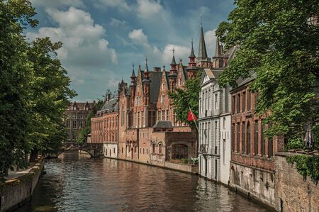 Wooded gardens and brick buildings on the canal edge in a sunny day at Bruges. With many canals and old buildings, this graceful town is a World Heritage Site of Unesco. Northwestern Belgium.