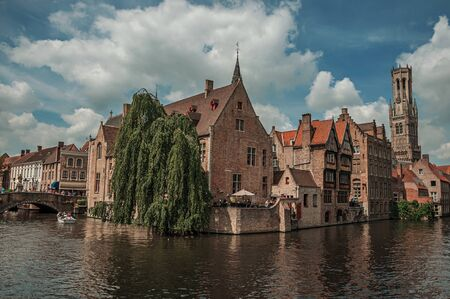 Bruges, Belgium - July 05, 2017. People and old buildings on the canal edge at Bruges. With many canals and old buildings, this graceful town is a World Heritage Site of Unesco. Northwestern Belgium