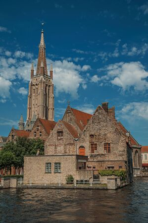 Steeple and old brick buildings on the canal edge in a sunny day at Bruges. With many canals and old buildings, this graceful town is a World Heritage Site of Unesco. Northwestern Belgium.