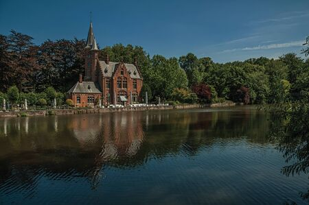 Amazing lake surrounded by greenery and old brick building on the other side in Bruges. With many canals and old buildings, this graceful town is a World Heritage Site of Unesco. Northwestern Belgium. Zdjęcie Seryjne