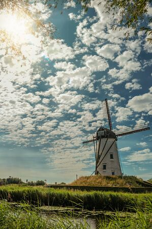 Old windmill next to canal with bushes and grove, sunlight and blue cloudy sky, near Damme. A quiet and charming countryside old village near Bruges. Northwestern Belgium. Retouched photo