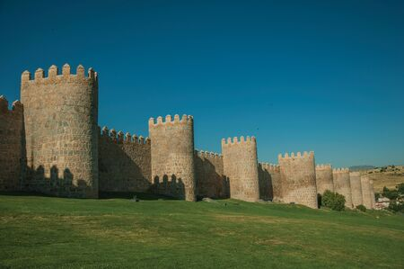 Lined stone towers on the large city wall in Romanesque style and green lawn, in a sunny day at Avila. It has the longest and imposing wall completely encircling this well-kept gothic town of Spain. Zdjęcie Seryjne