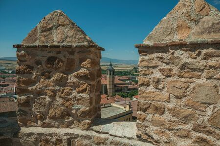 Church belfry amid roofs and hilly landscape seen from crenel in a stone wall around the town of Avila. It has the longest and imposing wall completely encircling this well-kept gothic town of Spain. Zdjęcie Seryjne