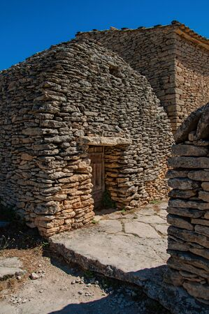 Typical hut made of stone with sunny blue sky, in the Village of Bories, near the town of Gordes. Located in the Vaucluse department, Provence region, in southeastern France