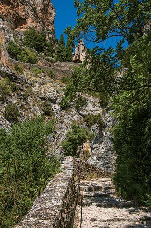 View of the Notre-Dame de Beauvoir church amidst cliffs and rocky pathway, above the graceful Moustiers-Sainte-Marie village. Alpes-de-Haute-Provence department, Provence region, southeastern France