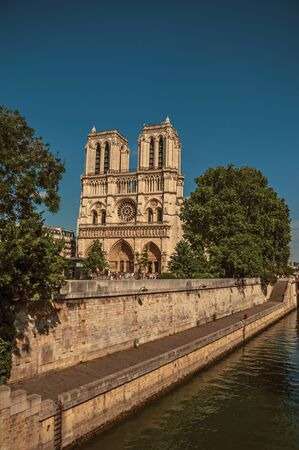 """People, tree-lined Seine River and gothic Notre-Dame Cathedral at Paris. Known as the """"City of Light"""", is one of the most impressive world's cultural center. Northern France. Retouched photo Zdjęcie Seryjne"""