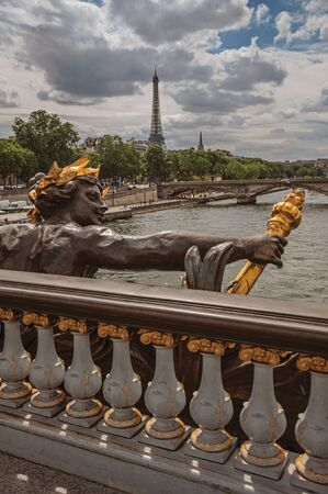 "Golden statue adorning the Alexandre III bridge over the Seine River and Eiffel Tower in Paris. Known as the ""City of Light"", is one of the most impressive world's cultural center. Northern France."