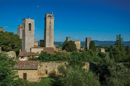 View of rooftops and towers with trees and blue sunny sky at San Gimignano. An amazing medieval town famous for having several towers in its historical center. Located in the Tuscany region