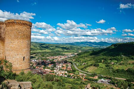 Overview of stone tower, green hills, vineyards and town rooftops near a road. From the city center of Orvieto, an ancient, pleasant and well preserved medieval town. Located in Umbria, central Italy