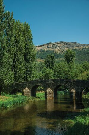 Old Roman stone bridge still in use over the Sever River, among leafy trees and undergrowth on sunny day at Portagem. A district of Marvão at the bottom of a lush wooded valley in eastern Portugal.