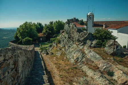 Church steeple and houses with whitewashed wall over rocky ridge, in a sunny day at Marvao. An amazing medieval fortified village perched on a granite crag in eastern Portugal. 스톡 콘텐츠