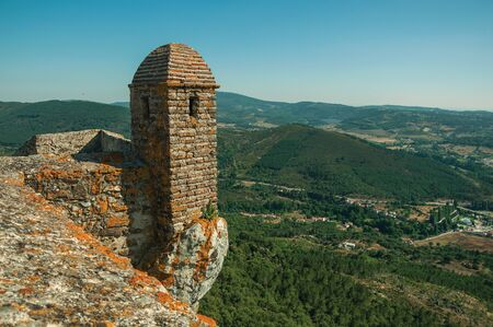 Small watchtower and stone wall over rocky cliff, with hilly landscape covered by trees in a sunny day at Marvao. An amazing medieval fortified village perched on a granite crag in eastern Portugal. 스톡 콘텐츠