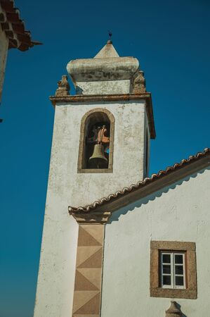 Old church steeple with bell decorated in baroque style and whitewashed wall, in a sunny day at Marvao. An amazing medieval fortified village perched on a granite crag in eastern Portugal. Zdjęcie Seryjne