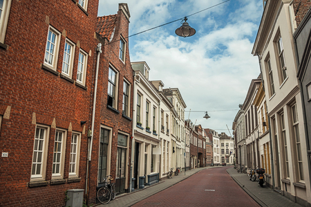 Empty street with semidetached brick houses and bicycles in front of doors at sunset and blue cloudy sky in s-Hertogenbosch. Gracious historical city with vibrant cultural life. Southern Netherlands. Publikacyjne