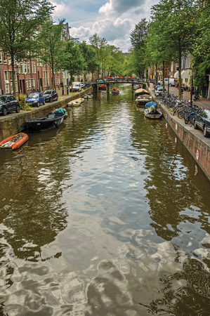 Amsterdam, northern Netherlands - June 26, 2017. Tree-lined canal with old brick buildings, boats and cloudy blue sky in Amsterdam. Famous for its huge cultural activity, graceful canals and bridges.