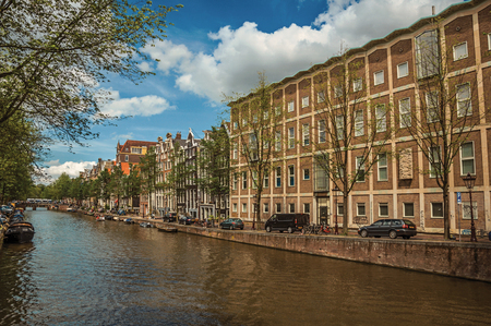 Amsterdam, northern Netherlands - June 26, 2017. Tree-lined canal with old brick buildings, boats and sunny blue sky in Amsterdam. Famous for its huge cultural activity, graceful canals and bridges.