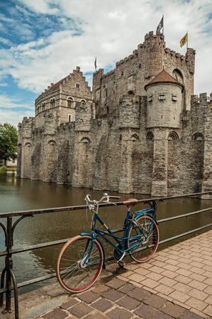Bridge and bike in front of Gravensteen Castle on cloudy day in Ghent. In addition to intense cultural life, the city is full of Gothic buildings and Flemish style architecture. Northern Belgium.