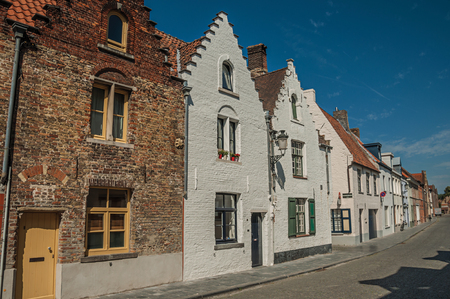 Bruges, Belgium - July 05, 2017. Brick facade of old houses with a blue sky in an empty street of Bruges. With many canals and old buildings, this graceful town is a World Heritage Site of Unesco. Publikacyjne
