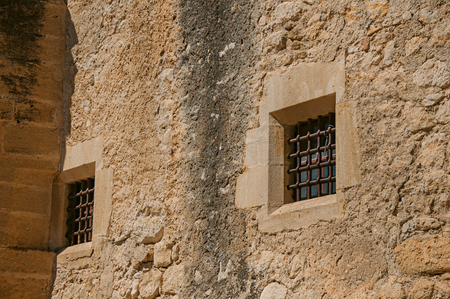 Close-up of the Lourmarin Castle walls and windows with bars, near the village of Lourmarin. In the Vaucluse department, Provence-Alpes-Cote d Azur region, southeastern France