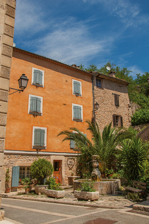 Chateaudouble, France - July 11, 2016. View of houses facing a square with fountain in Chateaudouble, a tourist village with medieval origin. Var department, Provence region, southeastern France