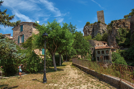 Chateaudouble, France - July 11, 2016. Child in a garden with trees, houses and cliff in Chateaudouble, a quiet and tourist village with medieval origin on a sunny day. Located in the Provence region. Publikacyjne