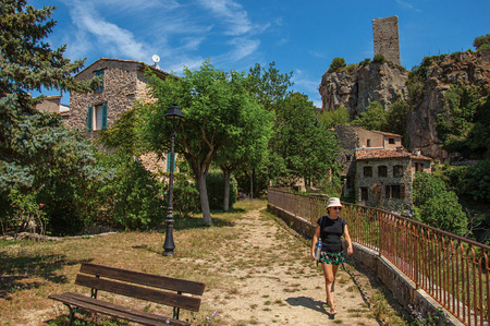 Chateaudouble, France - July 11, 2016. Woman in a garden with trees, houses and cliff in Chateaudouble, a quiet and tourist village with medieval origin on a sunny day. Provence region.