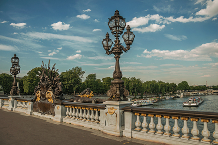 """Paris, France - July 07, 2017. People on elegant Alexandre III bridge over the Seine River in Paris. Known as the """"City of Light"""", is one of the most awesome world's cultural center. Northern France."""