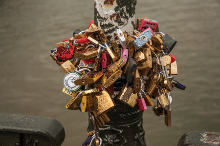 Paris, northern France - July 10, 2017. Padlocks fastened to each other celebrating love on pole over bridge at the Seine River in Paris. Known as one of the most impressive world's cultural center.