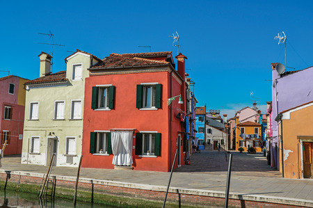 Burano, Italy - May 08, 2013. Overview of colorful buildings and clothes hanging in a blue sunny day at Burano, a gracious little town full of canals, near Venice. Veneto region, northern Italy Publikacyjne