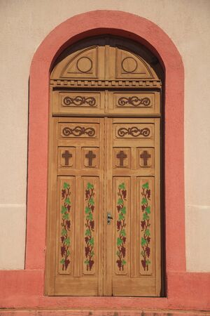 Wooden door decorated with grapevines painting on the facade of the St. Peter of the Stone Paths Chapel near Bento Goncalves. A friendly country town in southern Brazil famous for its wine production.