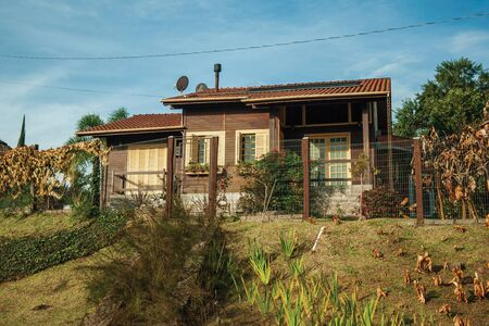 Charming wood house with fence and garden at sunset, near Bento Goncalves. A friendly country town in southern Brazil famous for its wine production.