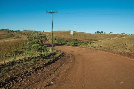 Deserted dirt road passing through rural lowlands called Pampas with green hills and trees near Cambara do Sul. A small country town in southern Brazil with amazing natural tourist attractions.