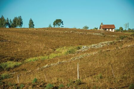 House on top of hill covered by dry bushes and rocks on lowlands called Pampas near Cambara do Sul. A small country town in southern Brazil with amazing natural tourist attractions.