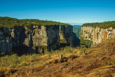 Dirt pathway aside the Itaimbezinho Canyon with steep rocky cliffs going through a flat plateau near Cambara do Sul. A small country town in southern Brazil with amazing natural tourist attractions.
