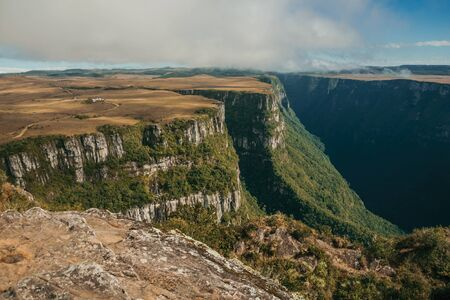 Fortaleza Canyon shaped by steep rocky cliffs with forest and flat plateau covered by dry bushes near Cambara do Sul. A small country town in southern Brazil with amazing natural tourist attractions. Zdjęcie Seryjne
