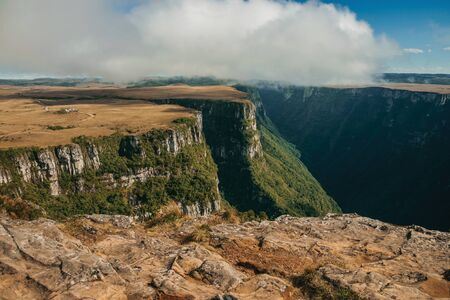 Fortaleza Canyon shaped by steep rocky cliffs with forest and flat plateau covered by dry bushes near Cambara do Sul. A small country town in southern Brazil with amazing natural tourist attractions.