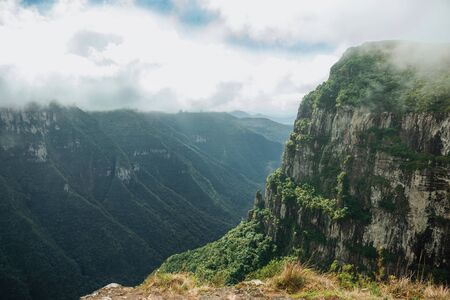 Fortaleza Canyon with steep rocky cliffs covered by thick forest and fog coming up the ravine near Cambara do Sul. A small country town in southern Brazil with amazing natural tourist attractions.