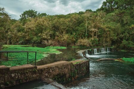 Stone dam in a river running through lush forest on a cloudy day at the Caracol Park near Canela. A charming small town very popular by its ecotourism in southern Brazil. Banque d'images