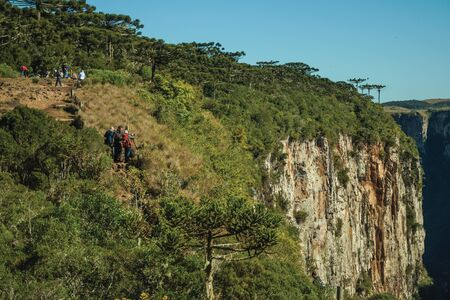 Cambara do Sul, Brazil - July 16, 2019. Dirt pathway and people at the Itaimbezinho Canyon with rocky cliffs near Cambara do Sul. A small country town with amazing natural tourist attractions.