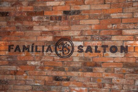 Bento Goncalves, Brazil - July 10, 2019. Sign on brick wall with the brand Salton Family in the Salton Winery, near Bento Goncalves. A friendly country town famous for its wine production.