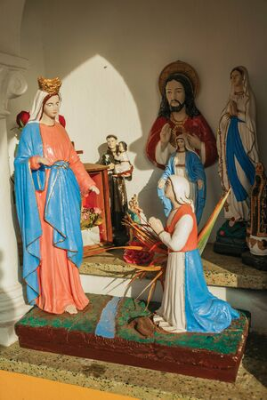 Bento Goncalves, Brazil - July 13, 2019. Statuettes of Virgin Mary and saints in Naive style made by unknown author in a shrine near Bento Goncalves. A country town famous for its wine production.
