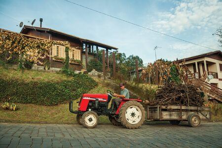 Bento Goncalves, Brazil - July 13, 2019. Tractor pulling cart with brushwood on a stone paved road, next to a wood house near Bento Goncalves. A friendly country town famous for its wine production.