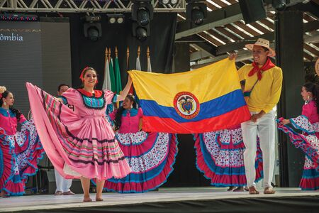 Nova Petropolis, Brazil - July 20, 2019. Colombian folk dancers with their national flag on stage of 47th International Folklore Festival of Nova Petropolis. A rural town founded by German immigrants.