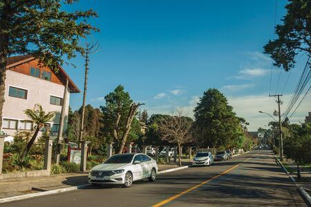 Gramado, Brazil - July 21, 2019. Empty paved street with parked cars and trees in a sunny day at Gramado. A cute european-influenced town highly sought after by tourists.