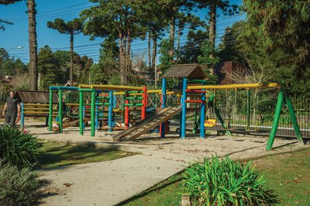 Gramado, Brazil - July 21, 2019. Colorful playground equipment among trees with children and adults playing in a sunny day at Gramado. A cute european-influenced town highly sought after by tourists. Redactioneel