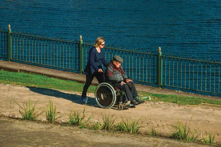 Gramado, Brazil - July 21, 2019. Woman pushing an elderly in wheelchair on pathway in front of Joaquina Rita Bier Lake at Gramado. A cute european-influenced town highly sought after by tourists.