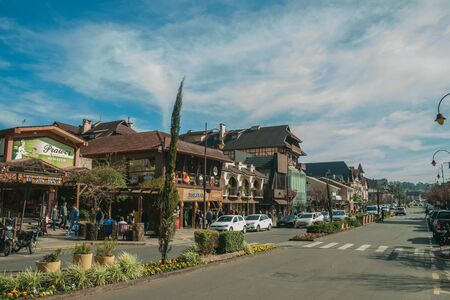 Gramado, Brazil - July 21, 2019. Buildings with shops and people on sidewalk at Borges de Medeiros Avenue, the main street of Gramado. A cute european-influenced town highly sought after by tourists.