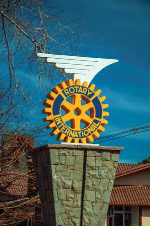 Gramado, Brazil - July 21, 2019. Rotary International logo sculpture on stone pedestal in sunny day at Gramado. A cute european-influenced town highly sought after by tourists.