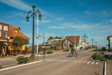 Cambara do Sul, Brazil - July 19, 2019. Flamboyant light poles and cyclist pedaling on the Getulio Vargas Avenue in Cambara do Sul. A small rural town with amazing natural tourist attractions. 에디토리얼
